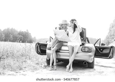 Full length of female friends reading map while leaning on convertible in countryside