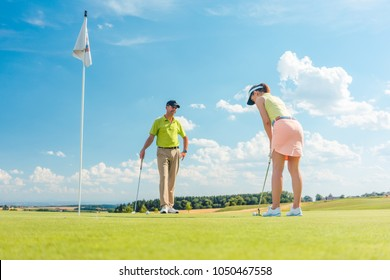 Full length of a female golf player ready to hit the ball with the club on the putting green, under the instruction of an experienced teacher outdoors in a sunny day