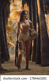 Full length female holding gun posing in palm trees forest on wild nature. Spirit of adventure. Survivor woman concept