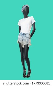 Full length female mannequin dressed in white t-shirt and blue jeans shorts, isolated on green background. No brand names or copyright objects.