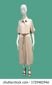 Full length female mannequin wearing fashionable brown dress, isolated on green background. No brand names or copyright objects.