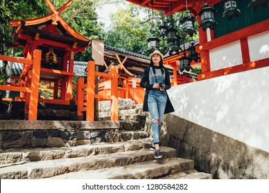 full length of female photographer walking down stone stairs outdoors visiting red wooden japanese temple in nara japan. young woman lens man sightseeing in kasuga grand shrine in summer.