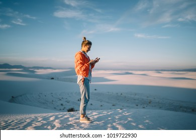 Full length of female traveler satisfied with good data connection sending messages on mobile phone during journey to White sands,hipster girl blogging via smartphone exploring desert in New Mexico