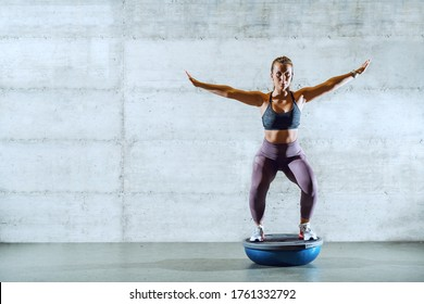 Full length of fit handsome young dedicated caucasian sportswoman in sportswear with ponytail balancing on bosu ball.