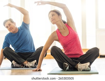 Full length of fit mature couple practicing yoga on mat at home