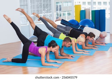 Full length of fit people exercising on fitness mats at gym