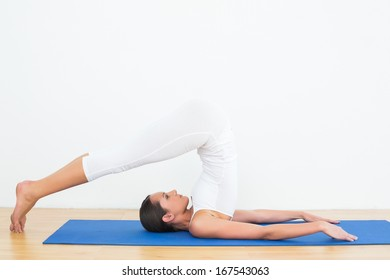 Full length of a fit young woman doing the plough posture in fitness studio