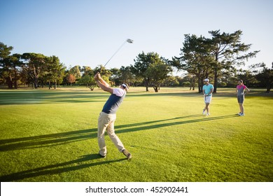 Full length of friends playing golf while standing on field