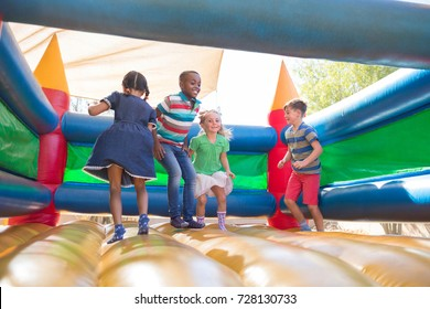 Full length of friends playing on bouncy castle at playground