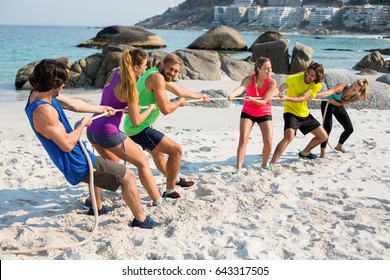Full length of friends playing tug of war on shore at beach