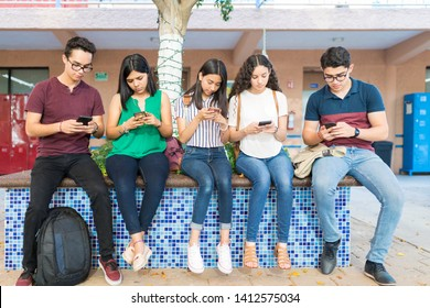 Full length of friends using mobile phones while sitting in high school campus