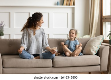 Full length front view smiling young curly mother sitting on comfortable couch with cute playful little preschool daughter in lotus position. Happy mommy practicing yoga exercised with small child.
