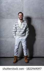 Full length frontal image isolated studio portrait of a young man in white jeans and cardigan, over concrete background.