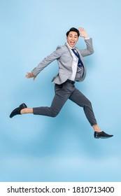 Volllanges lustiges Portrait eines fröhlichen jungen asiatischen Geschäftsmannes, der in der Luft springt einzeln auf Studioblauem Hintergrund
