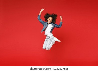 Full length of funny little african american kid girl 12-13 years old in denim jacket jumping showing victory sign isolated on red background children studio portrait. Childhood lifestyle concept