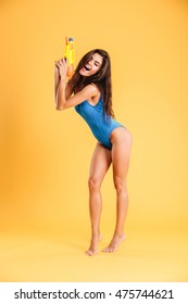 Full length of funny playful young woman in blue swimwear holding water gun with eyes closed over orange background