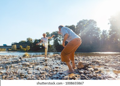 Full length of a funny senior couple playing with water at the river while enjoying their happy relationship in a sunny day of summer
