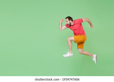 Full length funny young bearded man guy in casual red pink t-shirt posing isolated on green wall background studio portrait. People lifestyle concept. Mock up copy space. Jump like running celebrating