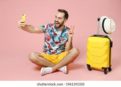 Full length funny young traveler tourist man sit on floor doing selfie shot on mobile phone showing victory sign isolated on pink background. Passenger travel on weekend. Air flight journey concept