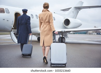 Full length girl and aviator keeping luggages while going to plain. They turning back to camera. Journey concept