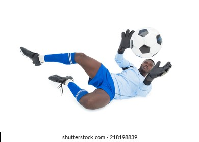 Full length of goal keeper in action over white background