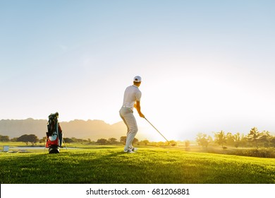 Full length of golf player playing golf on sunny day. Professional male golfer taking shot on golf course.