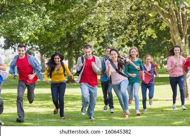 Full length of a group of college students running in the park