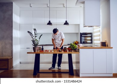 Full length of handsome caucasian creative chef standing in kitchen and cutting salmon for lunch. On kitchen counter are vegetables and spices.