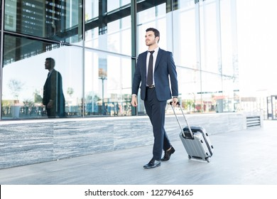 Full length of handsome young man in suit walking with luggage outside office building