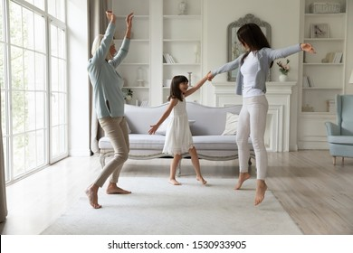 Full length happy 3 generations family having fun together in living room. Overjoyed little cute school girl dancing , jumping with happy young mommy and middle aged smiling grandmother at home.