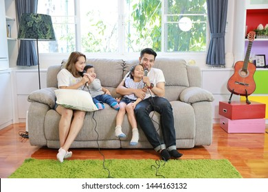 full length happy Asian family, father, mother daughter and son singing karaoke on the sofa in the living room with happy smiling face (relaxation and technology concept)
