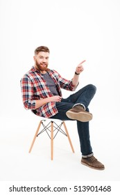 Full length of a happy bearded man pointing finger away at copyspace while sitting on the chair over white background