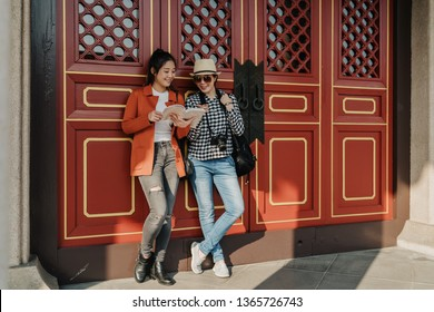 full length of happy beautiful asian women travelers stand leaning relying on wall red gate door of chinese temple reading looking guide book discussing. smiling female friends chatting point finger.