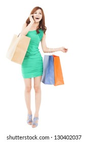 full length of Happy beautiful woman with shopping bags talking on the mobile phone