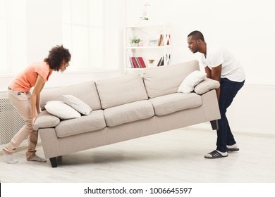 Full length of happy black couple placing sofa in living room of new home. Moving, interior design and real estate concept, copy space