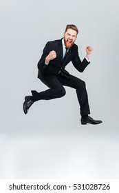 Full length happy business man in black suit jumping in studio and looking at camera with open mouth. Isolated gray background
