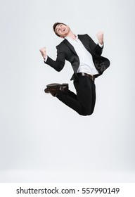 Full length happy business man in black suit jumping and celebrating success isolated on a white background