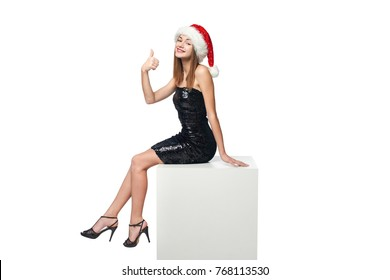 Full length happy Christmas girl in sequined dress and Santa sitting on big white box with blank copy space and gesturing thumb up