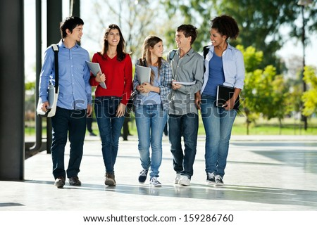 full length happy college students walking の写真素材 今すぐ編集