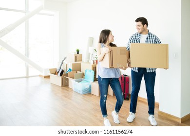 Full length of happy couple looking at each other while setting up new home
