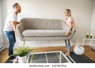 Full length of happy couple placing sofa in living room of new home
