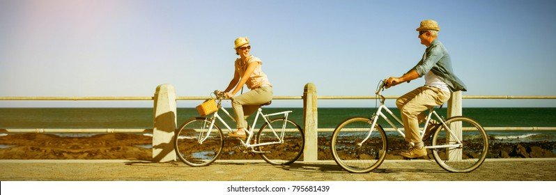 Full length of happy couple riding bicycles on pier against sea