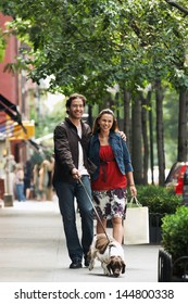 Full length of a happy couple walking dog on sidewalk