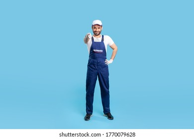 Full length happy courier in overalls, cap and protective gloves standing, pointing finger to camera, choosing you. Profession of service industry, loader or post delivery. indoor studio shot isolated