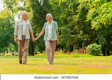Full length of happy elderly couple walking through a park