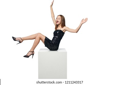 Full length happy excited girl in sequined dress sitting on big white box with blank copy space screaming of joy, isolated on white background