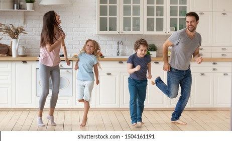 Full length happy father mother with overjoyed preschool school age two children having fun together at modern kitchen, dancing to music, jumping, enjoying bonding full family moment at home.