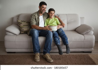 Full length of a happy father and son with popcorn bowl watching tv in the living room at home