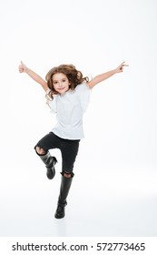 Full length of happy little girl jumping in the air over white background