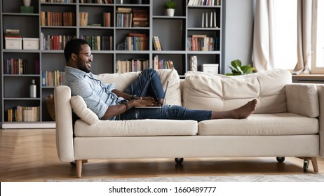 Full length happy millennial mixed race man relaxing lying on soft comfy sofa, enjoying communicating with friends in social network. Smiling young biracial guy dating, spending leisure time online.
